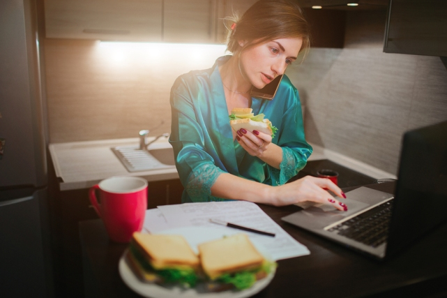 harried woman eating, drinking coffee, talking on the phone, working on laptop at the same time.