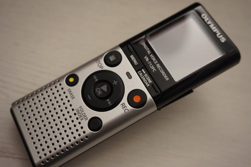 "A small hand-held Olympus digital recorder sits on a  wooden surface. It is not turned on. It is the kind of recorder made to be carried in a pocket or tucked away in a purse for short voice recordings and ""reminder"" memos. Photo credit: https://pixabay.com/photos/grabadora-mp3-recorder-retro-6080153/?fbclid=IwAR1S5YPfcJEyDa265qPsfPayvjDCkpnqbbG3Nd0r8OVP4VcyQXnoK16Ehms"