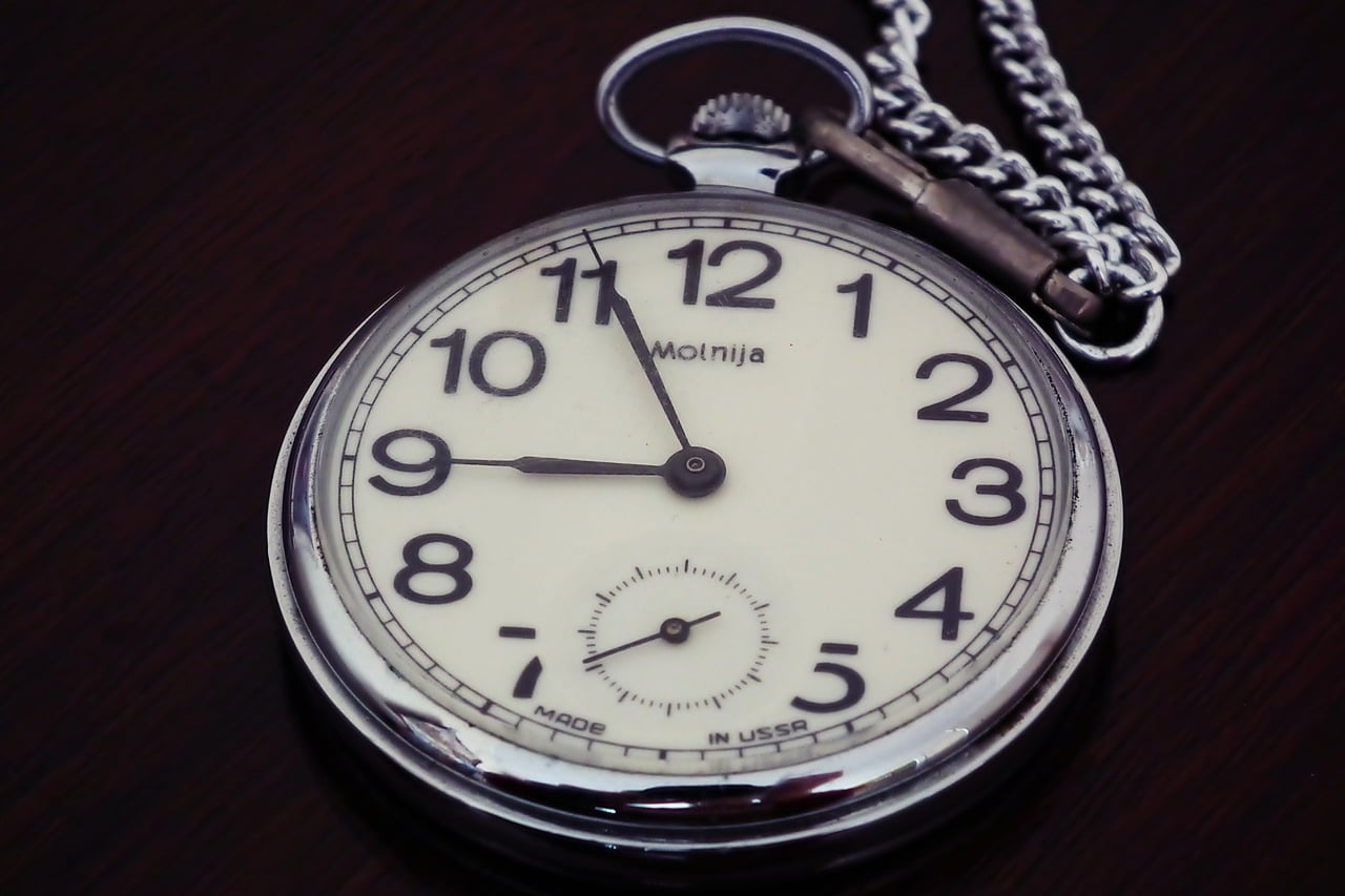 "A picture of an antique silver-colored pocketwatch on a black background. The face is creamy white. The numbers are black and larger than you might expect. The watch has a sweep second hand at the bottom and the circle of that small dial actually cuts off part of the ""5"" and ""7"". The face of the watch says  ""Molnija"" centered below the 12 with ""Made in USSR"" along the bottom. The time is 5 minutes until 9, and 40 seconds. The watch has a silver-colored chain but the clasp appears to be either tarnished or made of a metal similar to brass. Photo taken from: https://pixabay.com/photos/pocket-watch-time-antique-clock-6060604/?fbclid=IwAR0Gvn2xsORgFAsBzsNYe8dJdopL9djr4cWzS9Xqg5DqAAadcMnj3690YqQ"